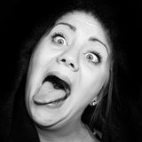 Crazy woman with staring eyes and outstretched tongue. In front of a black background Stock Photo
