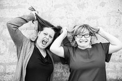 Crazy women. Scaring friends and having a good time in urban street Royalty Free Stock Images