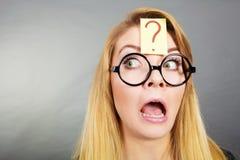 Weirdo nerd woman having question mark on forehead. Crazy wondering face expression concept. Wierdo nerd woman having question mark on forehead and geek Stock Photos