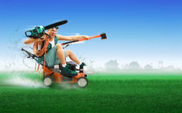 Crazy workman driving lawn mower. Crazy workman covered with instruments driving lawn mower over green grass Royalty Free Stock Images