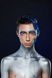 Crazy young androgyne man with face art. SPACEMAN. Freak person. Sperm on face. Tinsel creative blue makeup. Intersex and anorexia concept. Space for logo Stock Image