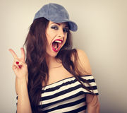 Crazy young female model in blue hat showing rock gesture with w. Ide opened mouth. Bright makeup and red lipstick. Toned vintage closeup portrait Royalty Free Stock Image
