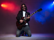 Crazy young guitarist playing electric guitar and shoing tongue Royalty Free Stock Photos