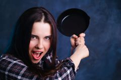 Crazy young housewife woman swinging with a pan. Cooking, culina royalty free stock photography