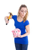 Crazy young and isolated blond woman breaking her pink piggy ban Stock Images