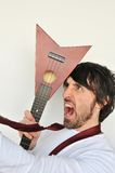 Crazy young man hiting his head with ukulele Royalty Free Stock Images