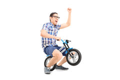 Crazy young man riding a small bike Royalty Free Stock Image