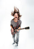 Crazy young man shaking head and playing electric guitar Royalty Free Stock Image