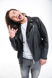 Crazy young man showing tongue and doing rock gesture. Crazy young man in black leather jacket showing tongue and doing rock gesture over white background Royalty Free Stock Images