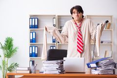 The crazy young man in straitjacket at the office. Crazy young man in straitjacket at the office stock photos