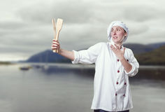Crazy young woman chef is singing with a wood utensils Stock Photography