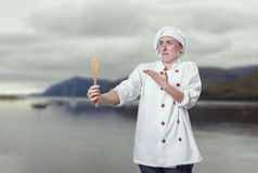 Crazy young woman chef is speaking with wood spoon Stock Image