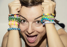 Crazy young woman with colorful rubber bracelets on her hands. Beauty and fashion Stock Images