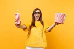 Crazy young woman in 3d imax glasses screaming, watching movie film, holding bucket of popcorn, plastic cup of cola or. Soda isolated on yellow background royalty free stock photos
