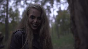 Crazy young woman with Halloween clown makeup on her face holding big knife in hand, laughing. The girl looking angrily. Crazy young woman with Halloween clown stock footage