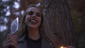 Crazy young woman with Halloween clown makeup on her face holding big knife and small candle in hands. The girl is. Crazy young woman with Halloween clown makeup stock footage