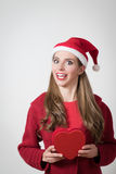 Crazy young woman holding a big heart present for Cristmas day Stock Images