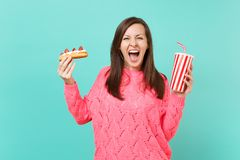 Crazy young woman in knitted pink sweater screaming, hold in hands eclair cake, plastic cup of cola or soda isolated on. Crazy young woman in knitted pink stock photos