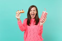 Crazy young woman in knitted pink sweater screaming, hold in hands eclair cake, plastic cup of cola or soda isolated on. Crazy young woman in knitted pink stock image