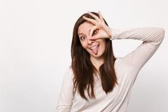 Crazy young woman in light clothes holding hands near eyes, imitating glasses or binoculars showing tongue isolated on. White background. People sincere royalty free stock photos