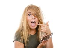 Crazy young woman talking on phone. Unpleasant conversation, bad relationships, concept. Crazy young blonde weirdo woman with messy hair talking on phone Royalty Free Stock Photo