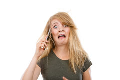 Crazy young woman talking on phone. Unpleasant conversation, bad relationships concept. Crazy young blonde weirdo woman with messy hair talking on phone. Studio Royalty Free Stock Photo