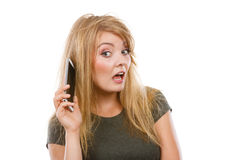 Crazy young woman talking on phone. Unpleasant conversation, bad relationships concept. Crazy young blonde weirdo woman with messy hair talking on phone. Studio Stock Image