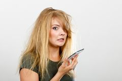 Crazy young woman talking on phone. Unpleasant conversation, bad relationships, concept. What did I say? Crazy young blonde weirdo woman with messy hair talking Stock Photography