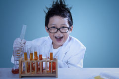 Crazzy scientist doing experiment. Cute asian boy wearing lab coat doing experiment like a mad scientist Stock Photos