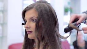 Creëren mooie natuurlijke krullen Brunette in een schoonheidssalon stock footage