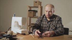 Crea la forma de un lazo de mariposa hecho de lanas Funcionamiento apuesto del hombre joven como sastre y usar una máquina de cos almacen de video
