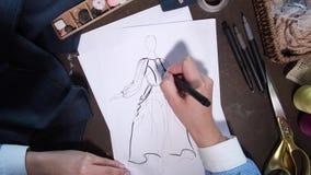 Creación del bosquejo por las manos del diseñador de ropa metrajes