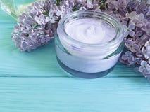 Cream косметическая бутылка сирени увлажнителя цветка на деревянном Стоковое Изображение