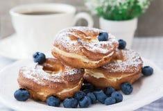 Cream слойки или печенье choux звенят с голубиками на плите Стоковая Фотография