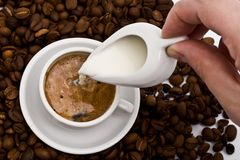 Cream being poured into coffee Royalty Free Stock Images