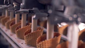 Ice-cream is being poured into waffle cones by automated tubes. Cream is being poured into waffle cones by automated tubes. 4K stock footage