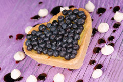 Cream and blueberry heart-shaped tart Stock Photography