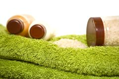 Cream bottles and bath salt on the towels. Isolated bottles and shower towels on white Royalty Free Stock Image
