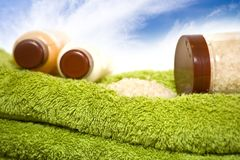 Cream bottles and bath salt on the towels. Isolated bottles and shower towels on sky Stock Image