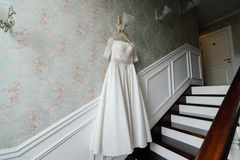 Cream bride dress hang on the lamp against the wall. Next to the stairs in the hotel Royalty Free Stock Photos