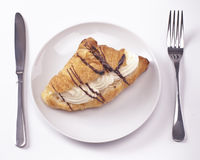 Cream bun. Cream cake with hints of chocolate on white plate with knife and fork royalty free stock photo