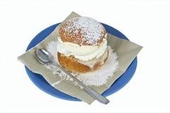 Cream bun with almond paste. On a plate Stock Photo