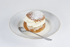 Cream bun with almond paste and hot milk. On a plate Stock Photo
