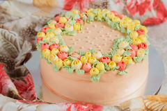 Cream cake decorated with small yellow and pink roses Royalty Free Stock Image