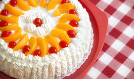 Cream cake with peaches and cherries Royalty Free Stock Image