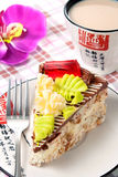 Cream cake. Piece of cake on a plate with fork and cup of tea on table Stock Photos