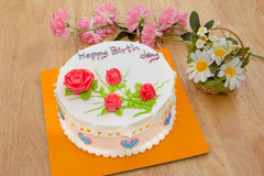 Cream cake with rose on the wooden table Royalty Free Stock Photos