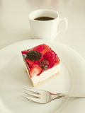 Cream cake with strawberries, raspberries. Blueberries, coffee and fork Royalty Free Stock Images