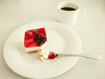 Cream cake with strawberries, raspberries. Blueberries, coffee and fork Stock Photo