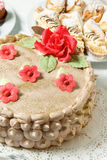 Cream cake with sugar red flowers. Baking sweets for dessert in the shop window Stock Photo